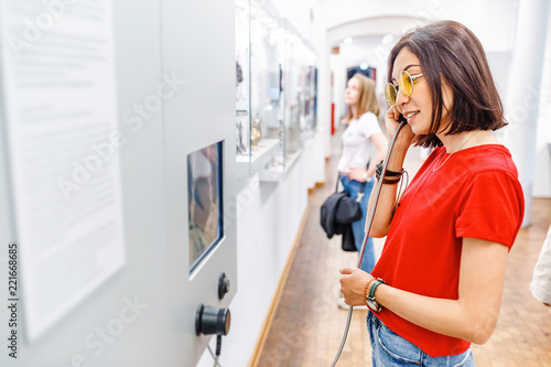 Fotografia Asian Woman looking at museum exhibition, and listening audio guide using headphones in modern gallery
