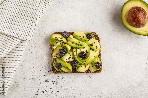Avocado toast on a healthy sesame bread with blackberry and sesame seeds, top view. Healthy vegan food concept.