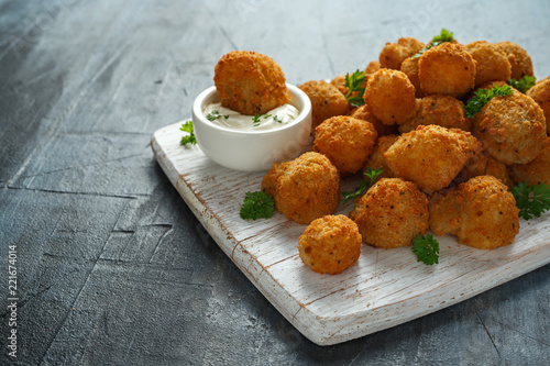 Photo Homemade Breaded Garlic Mushrooms with sour cream and parsley on white wooden bo