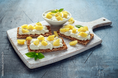 Homemade Crispbread toast with Cottage Cheese and Pineapple on white wooden board.