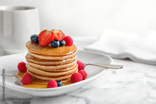 Tasty pancakes with berries and honey on plate