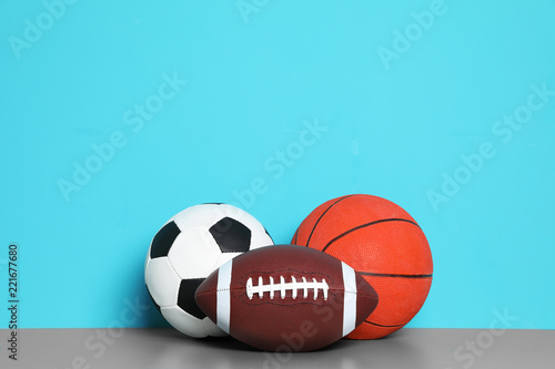Obrazy Sporty z Piłkami  different-sport-balls-on-table-against-color-background-space-for-text