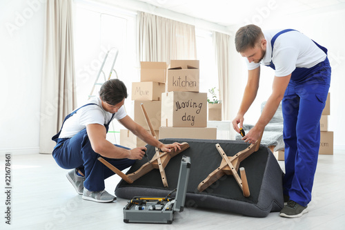 Male movers assembling sofa in new house Canvas Print