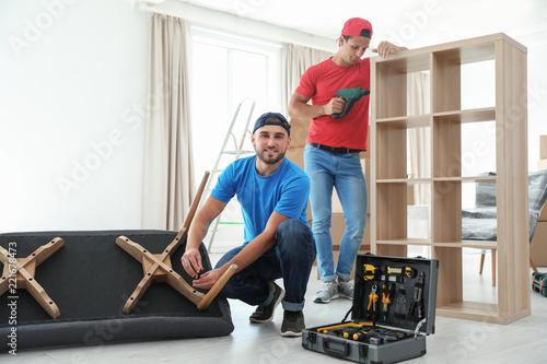 Fototapeta  Male movers assembling furniture in new house