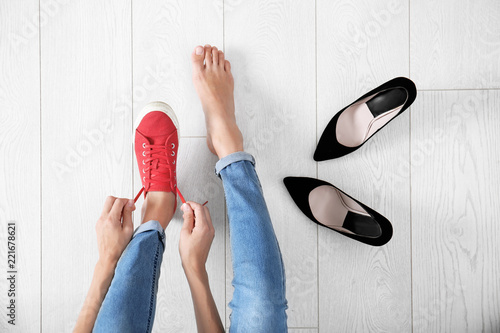 Young woman changing shoes on wooden background, top view