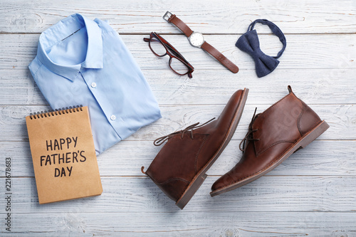 Flat lay composition with shoes, shirt and accessories on wooden background. Father's day celebration