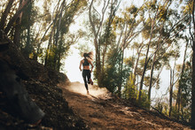 Woman Trail Running On A Mountain Path