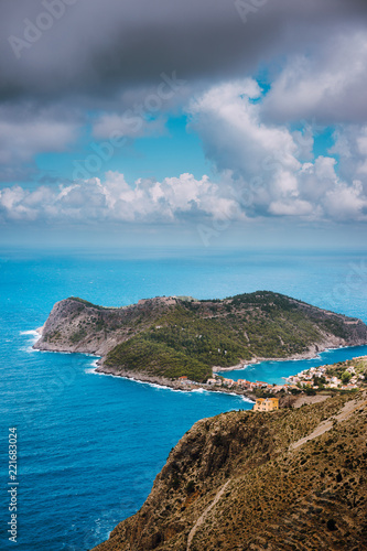 Foto  Cloudscape view of Assos village and blue sea bay
