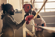 Boxing Kid Standing Inside A Boxing Ring Talking To His Coach