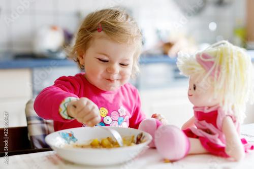 Fotografie, Obraz  Adorable baby girl eating from fork vegetables and pasta