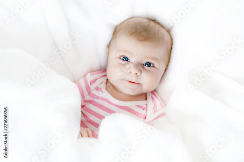 Cute adorable newborn baby in white bed on a blanket. New born child, little adorable girl looking surprised at the camera. Family, new life, childhood, beginning concept