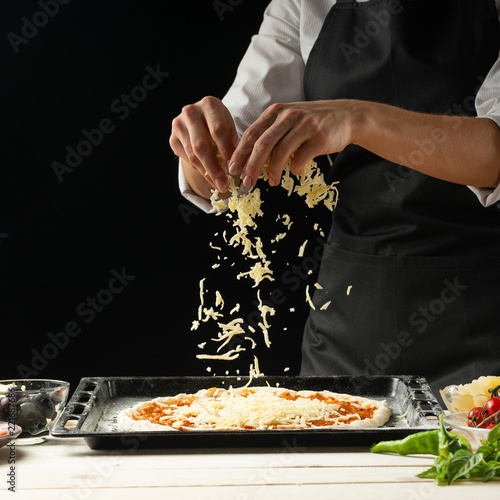 Fotografie, Obraz  The chef sprinkles the pizza with cheese on a dark background, with free space