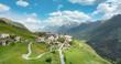 canvas print picture - Luftbild vom Dorf Guarda in der Gemeinde Scuol. im Hintergrund die Berge des Unterengadins Piz Pisco, Piz Ajüz.