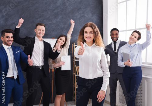 Fototapeta Happy businesswoman showing thumb up in office obraz