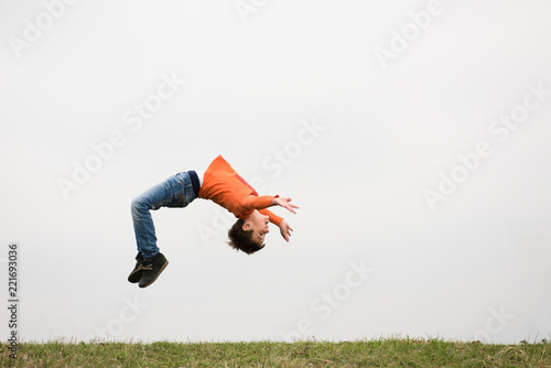 In de dag Gymnastiek healthy sport little boy jumping somersault outdoors nature with copyspace