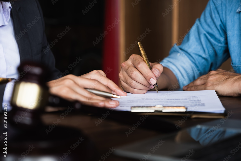Fototapeta Close up of an executive hands holding a pen and indicating where to sign a contract at office