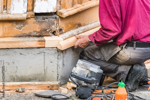 Fotografie, Tablou  A male carpenter crouched down assembling a piece of wood on a house, outdoors