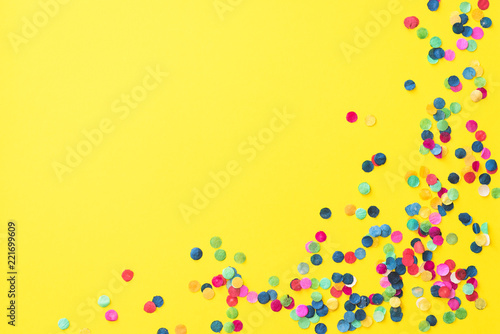 Obraz Flatlay of yellow background with colourful paper confetti in the corner and with copyspace - fototapety do salonu
