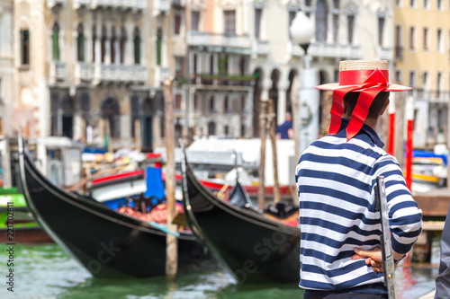 Gondolier standing next to gondola waiting for a client in Venice Italy