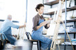 Young woman mixing colors on palette while sitting in front of easel with painting man on background