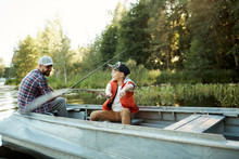 Happy Little Boy With Rod Showing His Father Where The Fish Is While Both Sitting In Boat