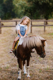Adorable little girl riding a pony at summer
