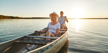 Smiling Young Couple Canoeing Together On A Lake In Summer