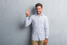 Handsome Young Business Man Over Grey Grunge Wall Wearing Elegant Shirt Showing And Pointing Up With Fingers Number Three While Smiling Confident And Happy.