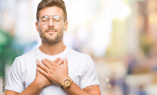 Obraz Young handsome man wearing glasses over isolated background smiling with hands on chest with closed eyes and grateful gesture on face. Health concept. - fototapety do salonu