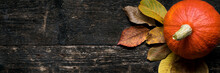 Autumn Harvest And Holiday Still Life. Happy Thanksgiving Bnner. Two Pumpkins And Fallen Leaves On Dark Wooden Background. Autumn Vegetables And Seasonal Decorations.