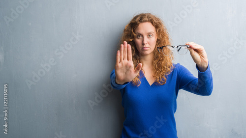 Fotomural  Young redhead woman over grey grunge wall holding optical glasses with open hand