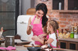 Young beautiful mother and her little daughter cooking together at the kitchen