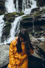 Smiling Woman In Yellow Raincoat With Waterfall On Background