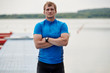 Portrait of young muscular athlete standing outdoors near the lake