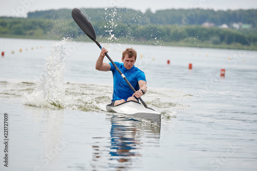 Fotografie, Obraz Young man kayaking on the lake, he is competing in rowing