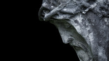 An Ancient Statue Of The Crucifixion Of Jesus Christ In Profile Against Black Background