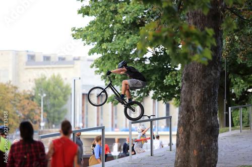 Młody mężczyzna skacze na rowerze przez barierkę na Wrocławskim bulwarze.