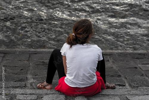 Vászonkép Ragazza seduta di spalledi fronte al lago