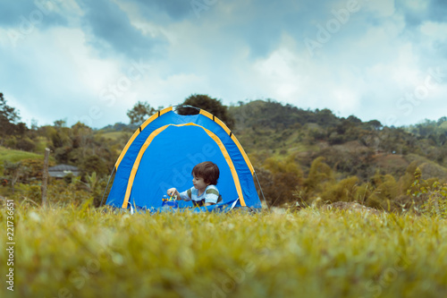 Fotografie, Obraz  open shot of a landscape where a child is seen playing inside a tent with the cl