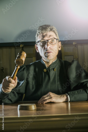 Fotografija  judge with a hammer in his hand in the court room