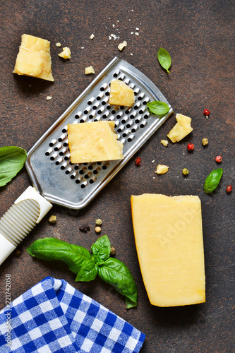 Parmesan cheese, garlic, basil on a concrete dark background. Ingredients for pasta. Advertising food.