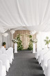 Wedding decoration, ceremony in a light tent, chairs and arch. Gorgeous bouquet of different flowers. White floral arrangement in vintage vase.