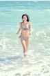 Girl in a bikini runs into the sea