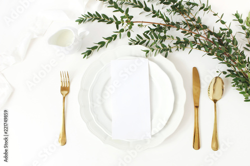 Festive wedding, birthday table setting with golden cutlery, eucalyptus parvifolia branch, porcelain plate, milk and silk ribbon. Blank card mockup. Rustic restaurant menu concept. Flat lay, top view
