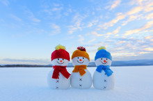 Three Small Snowman In Colorful Hats Are Standing On The Snow. The Scenery With Mountains, Field In Snow, Blue Sky. Beautiful Winter Day.