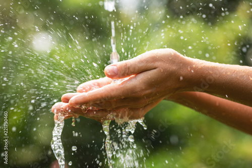Fotografia  Wet female hands and clear water splashes