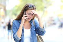Worried Woman Having A Phone Conversation In The Street