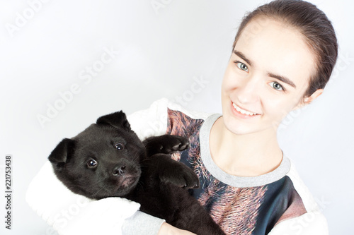 Fotografia  A happy teenage girl holding a German shepherd puppy in her arms