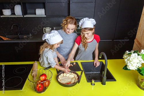 Poster Cuisine Happy family in kitchen. Mother and two children preparing dough, bake apple pie. Mom and daughters cooking healthy food at home and having fun. Household, teamwork helping, maternity concept