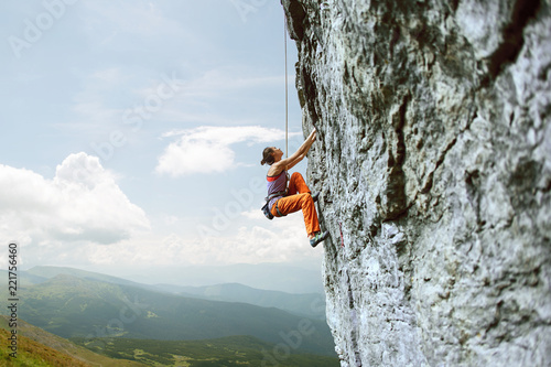 young slim female rock climber climbing on the cliff Fototapeta